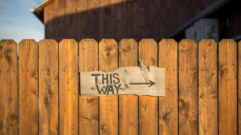 Ein Holzzaun mit einem Schild, was zeigt, dass nach rechts gegangen werden soll.
