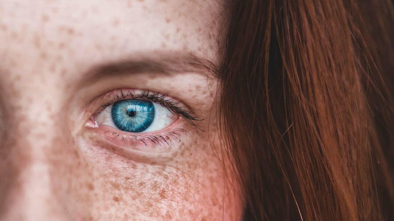 Nahaufnahme von einem blauen Auge einer rothaarigen Frau mit Sommersprossen.
