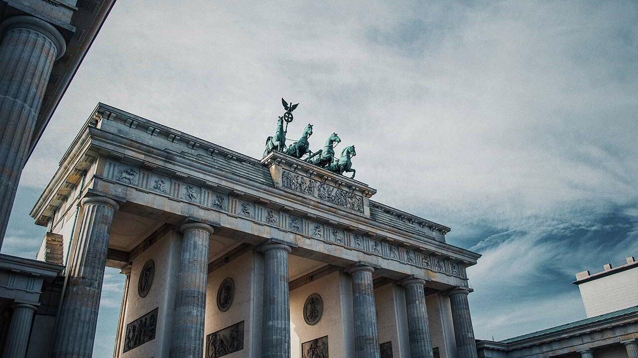 Das Brandenburger Tor vor einem bewölkten Himmel.