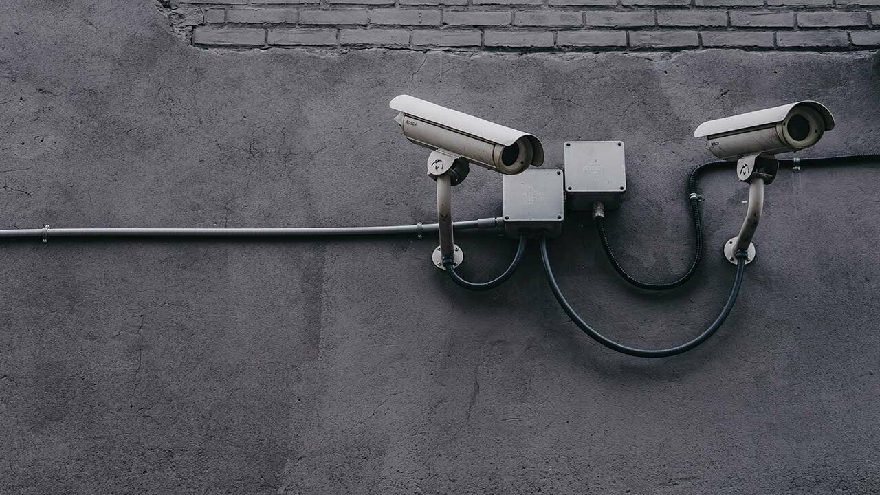 Zwei Überwachungskameras an einer grauen Fassade.