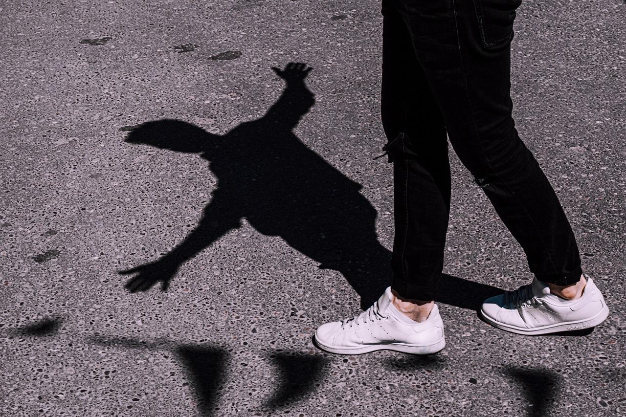 Mensch läuft auf Straße. Sein Schatten zeigt, dass er die Arme ausgestreckt hat