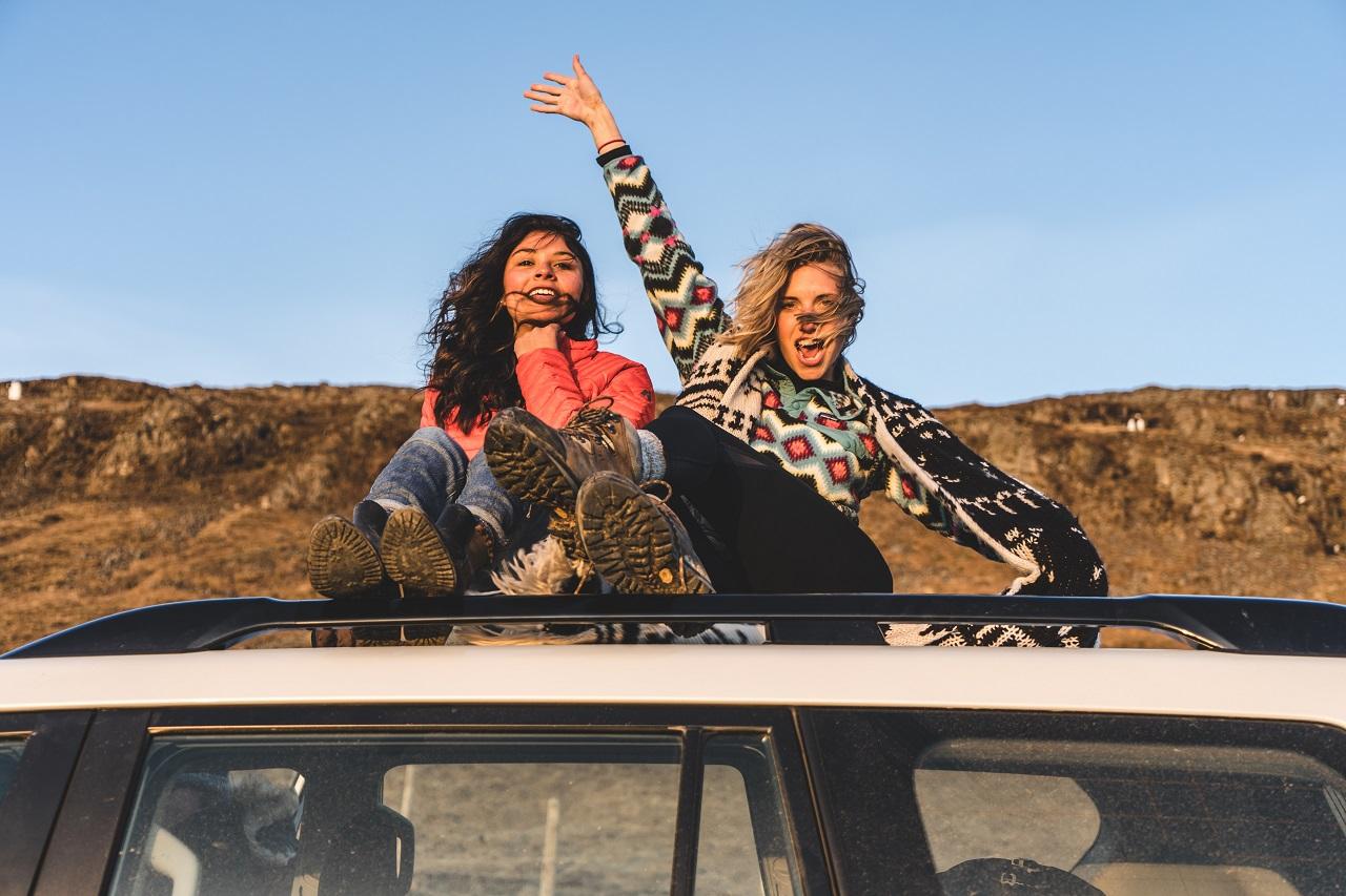 Zwei Frauen sitzen auf einem Autodach in den Bergen und Winken